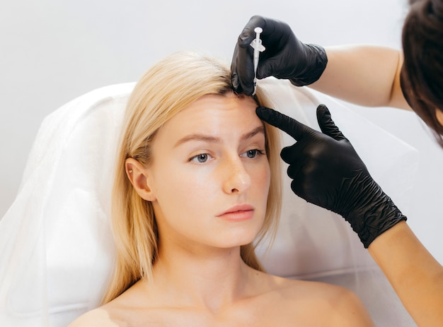 Portrait of attractive blonde model making injection in forehead