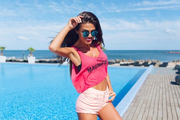 Ritratto di attraente ragazza bruna con i capelli lunghi in posa per la fotocamera vicino alla piscina. lei sta sorridendo.