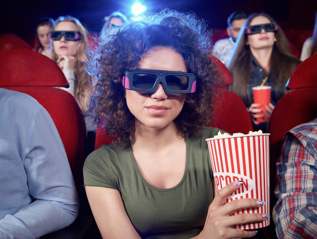 Portrait of attractive brunette, smiling and posing during film in cinema hall. pretty girl eating popcorn and watching funny interesting comedy. concept of entertainment.