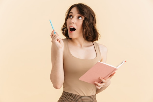 Portrait of attractive brunette woman dressed in casual clothes smiling while holding and writing notes in diary book isolated