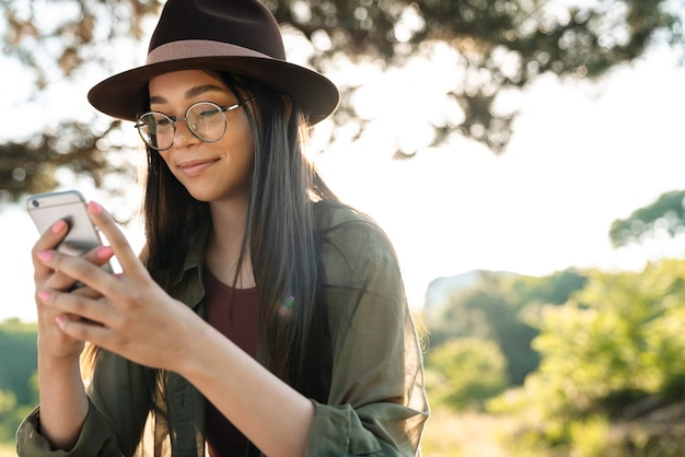 Portrait of attractive brunette woman wearing stylish hat and eyeglasses using cellphone while walking in green park on sunny day