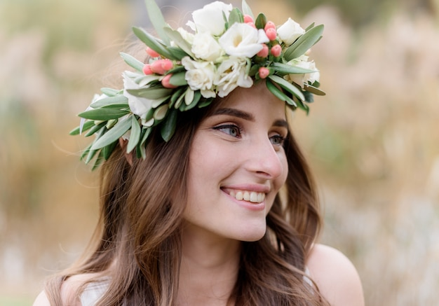 Portrait of an attractive brunette woman in a wreath made of eustomas with a beautiful smile