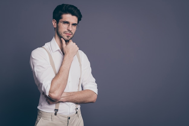 Portrait of attractive business man charming appearance holding arm on chin deep minded dressed formalwear white shirt beige suspenders specs .