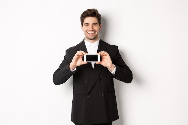 Ritratto di uomo d'affari attraente in abito nero, tenendo lo smartphone in orizzontale e mostrando lo schermo, sorridendo compiaciuto, in piedi su sfondo bianco