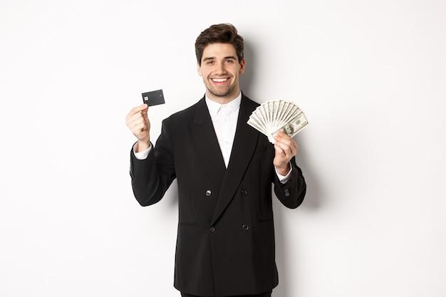Ritratto di uomo d'affari attraente in abito nero, mostrando soldi e carta di credito, sorridente soddisfatto, in piedi su sfondo bianco.