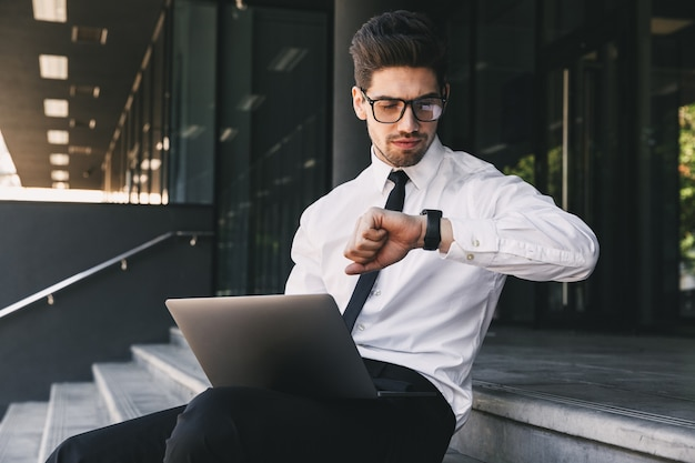 Portrait of attractive businessman dressed in formal suit sitting outside glass building with laptop, and looking at his wrist watch