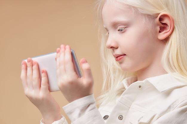 Portrait of attractive caucasian albino girl with smartphone
