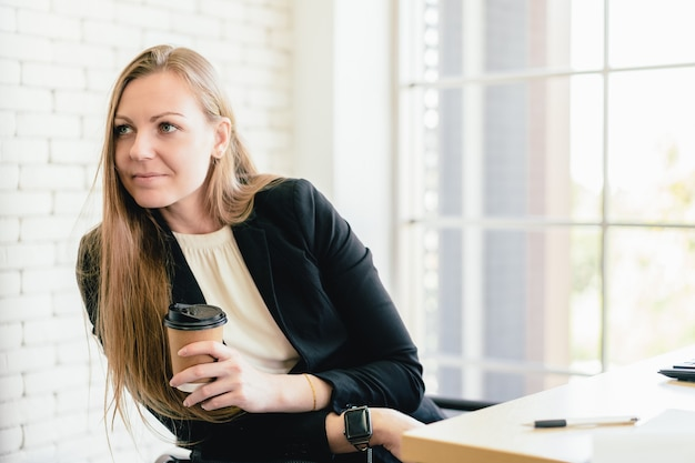Portrait of attractive caucasian businesswoman holding a coffee cup and intentionally listening to another employee with copy space.
