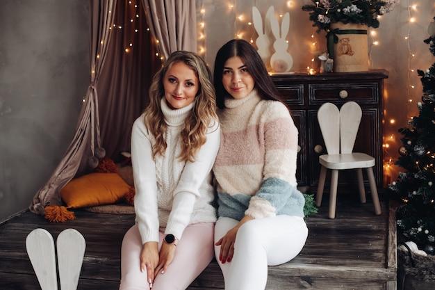 Il ritratto delle amiche caucasiche attraenti celebra modestamente il natale insieme