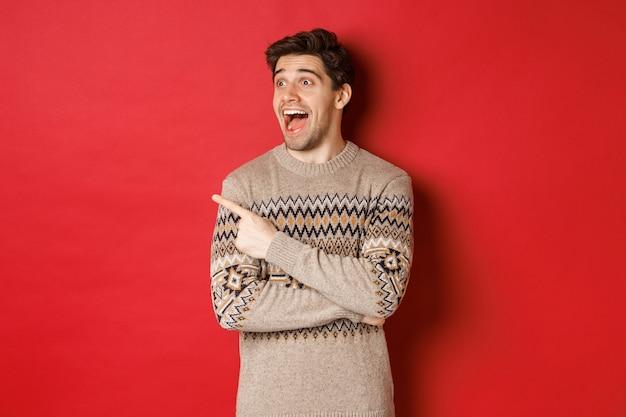 Ritratto di uomo caucasico attraente che celebra il nuovo anno, le vacanze invernali, puntando il dito e guardando a sinistra con espressione stupita, mostrando la pubblicità di natale, in piedi su sfondo rosso.