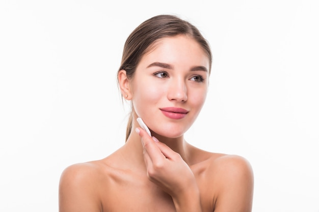 Portrait of attractive caucasian smiling woman cleaning her face isolated on white wall