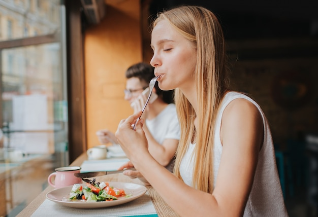 Portrait of attractive caucasian smiling woman eating salad
