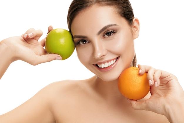 Il ritratto della donna sorridente caucasica attraente isolata sulla parete bianca dello studio con la mela verde e la frutta arancione. la bellezza, la cura, la pelle, il trattamento, la salute, la spa, i cosmetici e il concetto di annuncio