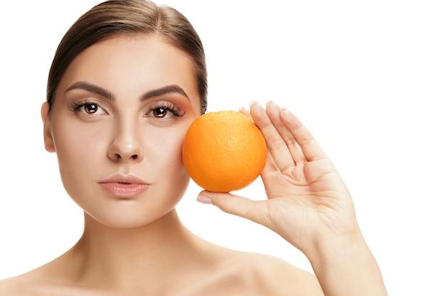 Il ritratto della donna sorridente caucasica attraente isolata sul muro bianco con frutta arancione. la bellezza, la cura, la pelle, il trattamento, la salute, la spa, i cosmetici