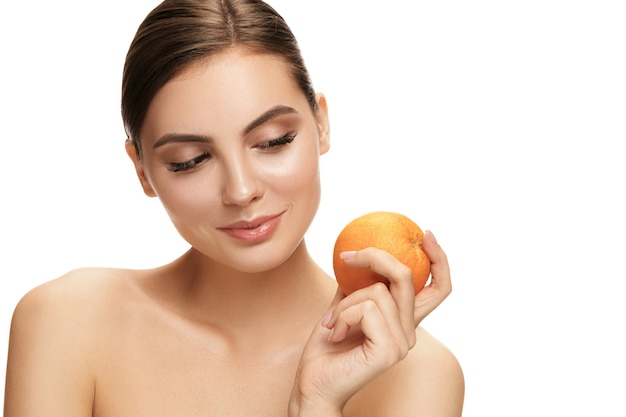 The portrait of attractive caucasian smiling woman isolated on white wall with orange fruit.