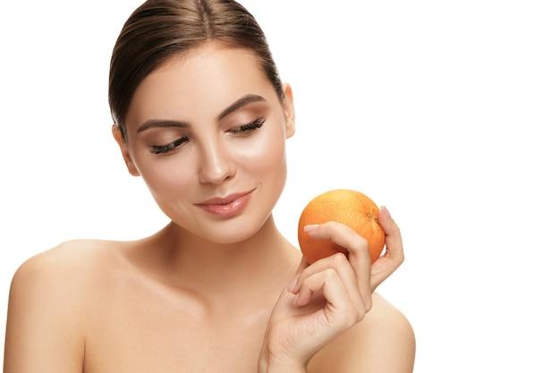 Il ritratto della donna sorridente caucasica attraente isolata sul muro bianco con frutta arancione.