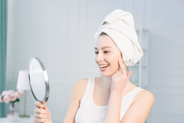 Portrait of attractive caucasian smiling woman on white studio shot cleaning her face looking at the mirror applying foundation on facial skin