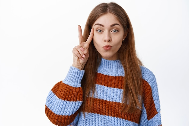 Portrait of attractive caucasian woman pucker lips, making kissing face and showing v-sign peace gesture near cheek, posing kawaii, standing over white wall
