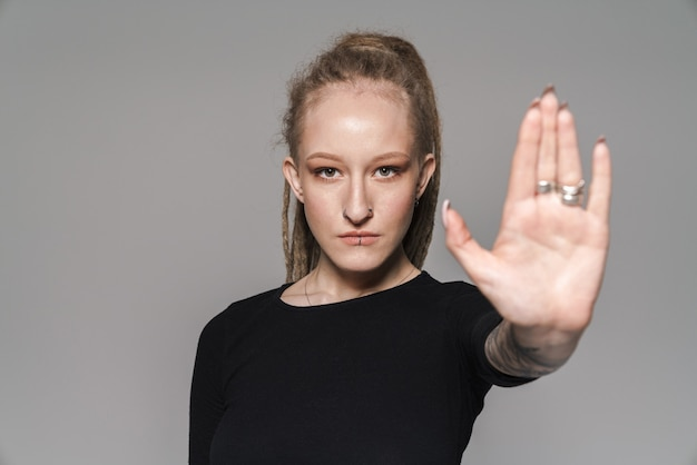 Portrait of an attractive confident young woman with dreadlocks standing isolated, showing stop gesture