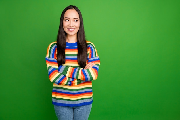 Portrait of attractive content cheery girl folded arms looking aside copy empty space isolated over bright green color background