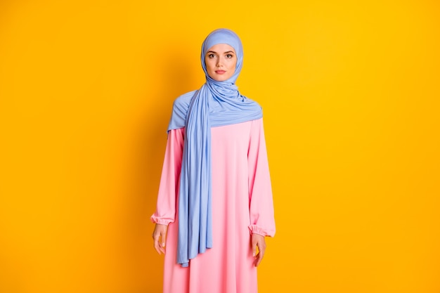 Portrait of attractive content shy modest muslimah wearing cozy dress isolated over bright yellow color background