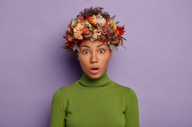 Portrait of attractive curly haired adult woman looks with shock at camera, feels stupefied and amazed, keeps mouth opened, wears autumn wreath on head, poses in studio against purple background