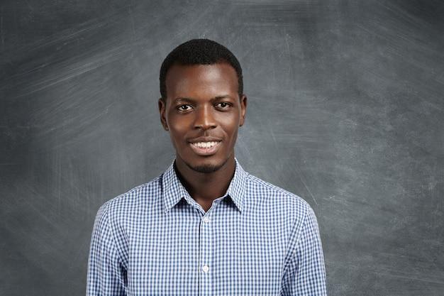 Ritratto di attraente studente dalla carnagione scura che indossa camicia a scacchi con espressione fiduciosa e gioiosa, in piedi sulla parete della lavagna