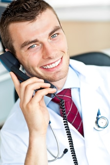 Portrait of an attractive doctor talking on phone smiling at the camera