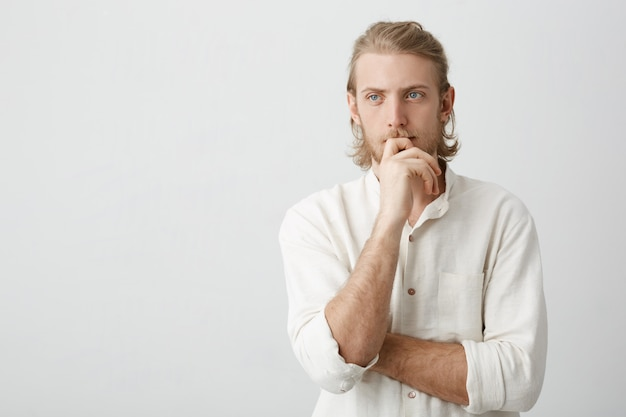 Portrait of attractive european businessman with ponytail hairstyle and beard, holding hand on chin while looking aside