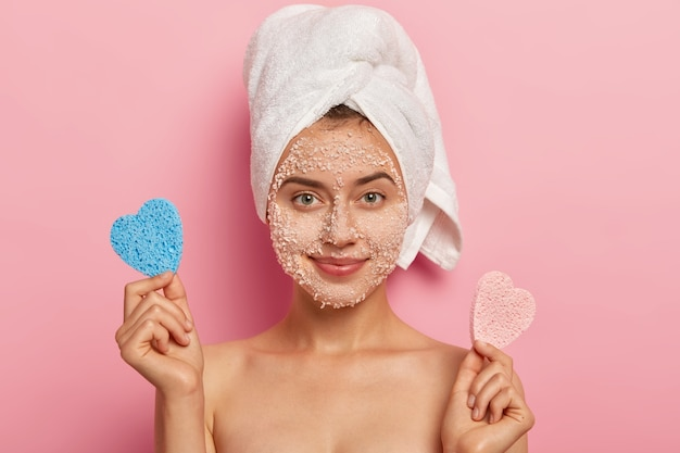 Portrait of attractive european charming woman with sea salt scrub on complexion, wears wrapped soft towel on head, has healthy skin, poses shirtless against rosy background, has tender look
