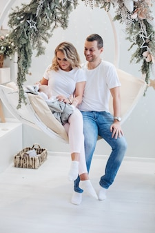 Portrait of attractive family having fun with baby sitting on cozy swing decorated with fir branches.