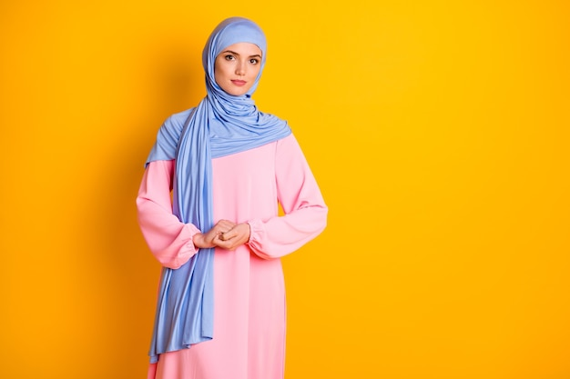 Portrait of attractive fashionable peaceful modest muslimah wearing cosy dress isolated over bright yellow color background