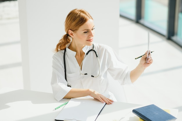Portrait of attractive female doctor holding clipboard while standing in clinic