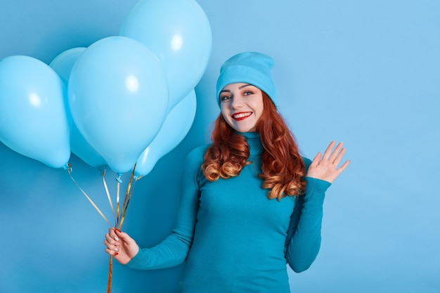 Portrait of attractive female holding in hand bench of balloons