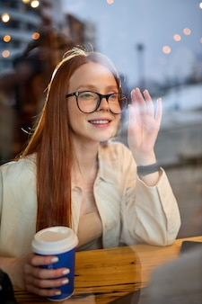 Portrait of attractive female photographer journalist with red hair sitting at cafe working