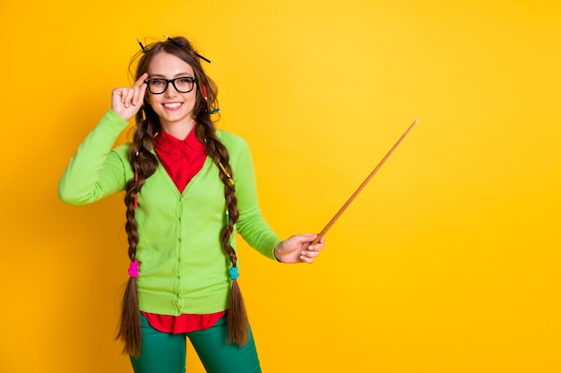 Portrait of attractive funky cheerful clever girl pointing demonstrating subject teaching copy space isolated over shine yellow color background
