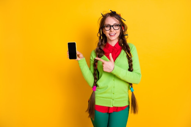 Portrait of attractive funky cheerful teenage schoolgirl demonstrating device isolated over bright yellow color background