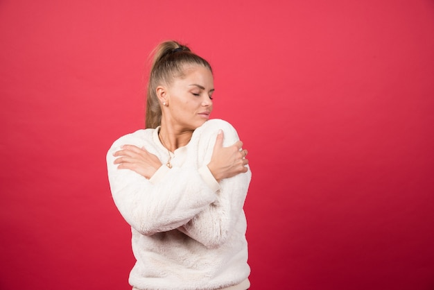 Portrait of an attractive girl hugging herself isolated over red wall