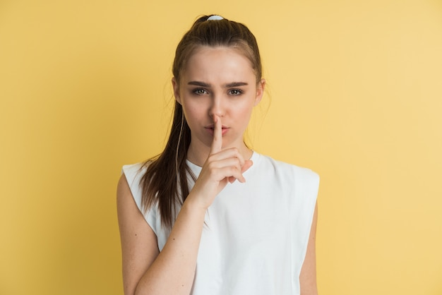 Portrait of attractive girl with finger on lips, isolated over yellow background.
