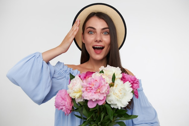 Portrait of attractive girl with long brunette hair. wearing a hat and blue dress. holding bouquet of flowers and touching her head, surprised. watching  isolated over white wall