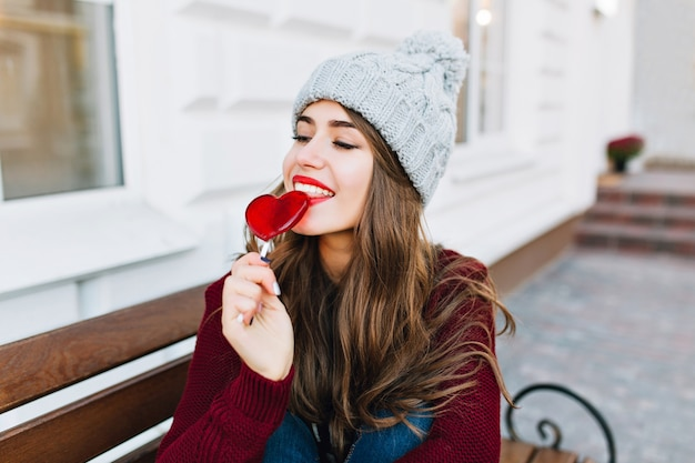 Ragazza attraente del ritratto con capelli lunghi in cappello lavorato a maglia sulla strada. tiene gli occhi chiusi, guarda divertita a leccare il cuore di caramello.