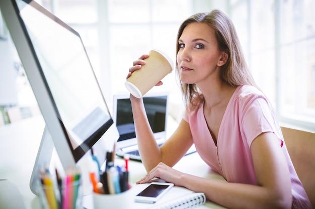 Portrait of attractive graphic designer drinking coffee