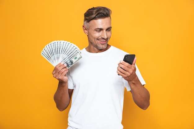 Portrait of attractive guy 30s in white t-shirt holding cell phone and bunch of money isolated on yellow