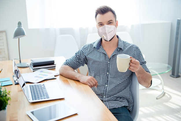 Portrait of  attractive guy wearing n95 reusable mask working remotely cov ncov mers disease pandemia preventive measures drinking tea in light office work place station