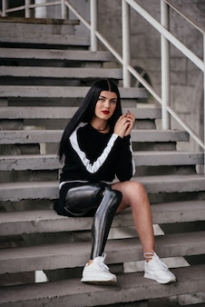 Portrait of attractive handicapped woman in black tracksuit with prosthetic leg