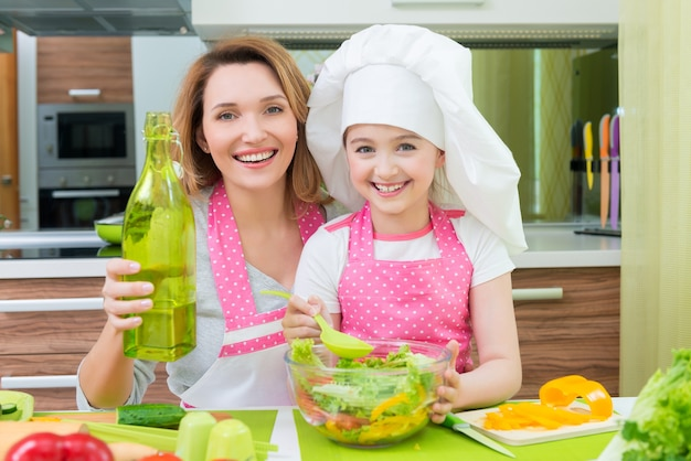 Portrait of attractive happy mother and daughter cooking a salad at the kitchen.