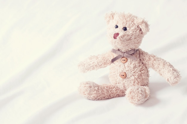 Portrait of an attractive happy teddy bear smiling ,cute teddy bear lying on white fabric background.