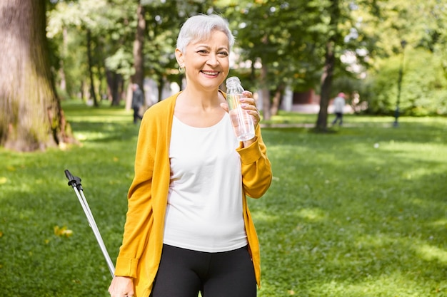 Portrait of attractive healthy senior woman with pixie gray hair having rest while walking in park using nordic scandinavian poles, holding bottle, drinking water, feeling full of energy, smiling