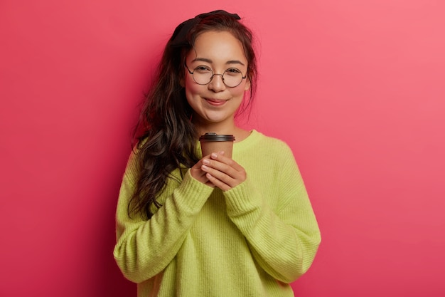 Portrait of attractive korean girl stands with takeaway coffee, enjoys caffeine beverage, looks with tender happy expression