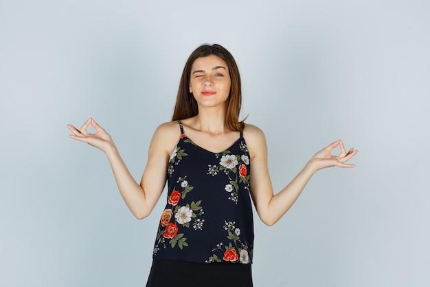 Ritratto di una donna attraente che mostra il gesto dello yoga mentre sbatte le palpebre in camicetta e sembra una vista frontale pacifica